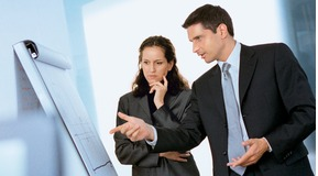 Businessman and Businesswoman discussing in front of a flip-chart.