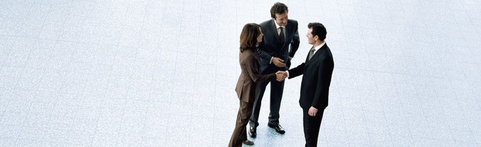 Three business people, man and woman shaking hands.